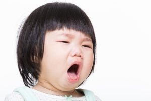 Asian toddler-age girl preparing to sneeze