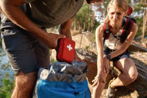 Young man pulling first aid kit out of a backpack while young woman holds knee and has pained expression on her face - both appear to be hiking in the woods