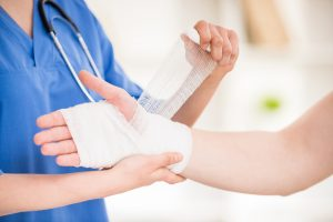 Torso of medical professional in scrubs wrapping gauze around that hand and wrist of a patient whose right arm only is in view