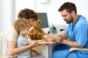 Mother holding curly-haired preschooler who is stretching out right arm and hand for a young male medical professional wearing scrubs and a stethoscope to see