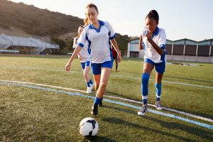 Trio of teenage girls of different ethnicities in soccer uniforms running across a field with the foreground girl preparing to kick a soccer ball