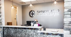 Attractive reception desk with staff member sitting at computer and Springfield Urgent Care logo on the wall behind her