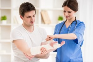Young female medical professional in scrubs wraps a young male patient's forearm and hand with a bandage